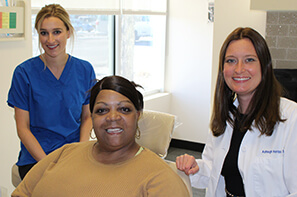 female dental assistant in blue shirt, female dental patient wearing tan shirt and female dentist wearing white lab coat