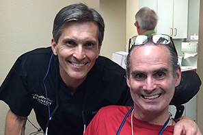 Male volunteer dentist with male patient in red shirt
