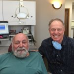 Two older gentlemen - one in a dentist chair on the left and dentist on the right