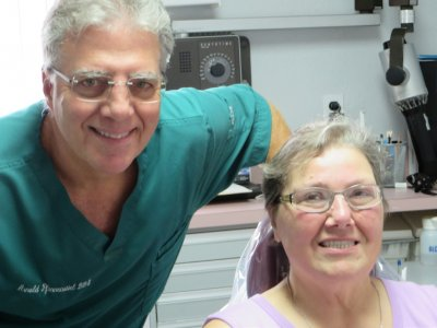 Older male dentist in green scrub and older woman patient in pink shirt